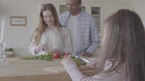 Homem afro-americano e mulher consideravelmente de sorriso que cozinham a posição da salada na tabela na cozinha moderna Bailarin video estoque