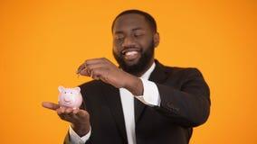 Homem afro-americano econômico no terno que põe a moeda no mealheiro, economias, depósito video estoque