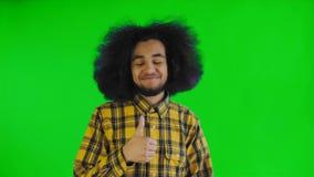 Homem afro-americano feliz novo que sorri ao dar os polegares acima na tela verde ou no fundo chave do croma Conceito de filme