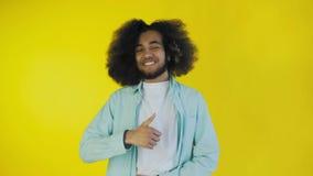 Homem afro-americano feliz novo que sorri ao dar os polegares acima no fundo amarelo Conceito das emo??es filme