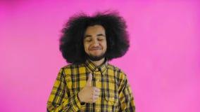 Homem afro-americano feliz novo que sorri ao dar os polegares acima no fundo roxo Conceito das emo??es video estoque