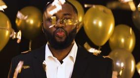 Homem afro-americano na posição do terno sob os confetes de queda, enviando o beijo do ar filme