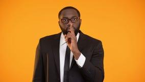 Homem afro-americano no terno que mostra o sinal quieto, bisbolhetices, divulgação pessoal dos dados filme