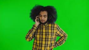 Homem afro-americano novo atrativo feliz que fala no telefone celular na tela verde ou no fundo chave do croma Conceito de vídeos de arquivo