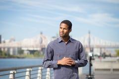 Homem afro-americano novo com o rio e ponte na parte traseira imagens de stock