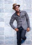 Homem afro-americano novo considerável que inclina-se contra a parede Fotos de Stock