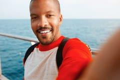 Homem afro-americano novo de sorriso considerável do moderno que toma o selfie com ar livre feliz da cara da cidade Mar azul no foto de stock