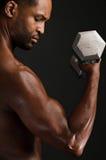 Homem afro-americano novo que dobra o bíceps Foto de Stock Royalty Free
