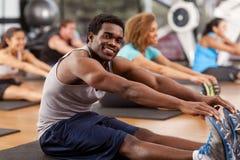 Homem afro-americano novo que estica em um gym Fotografia de Stock Royalty Free