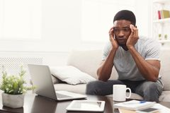 Homem afro-americano novo que tem a dor de cabeça em casa imagem de stock royalty free