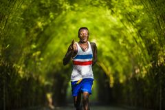 Homem afro-americano preto atlético e atrativo novo do corredor que faz o ar livre de corrida do treinamento do exercício no parq fotos de stock