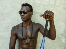 Homem afro-americano preto atrativo e considerável novo com corpo muscular apto e seis bastões de beisebol da terra arrendada d fotografia de stock