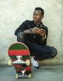 Homem afro-americano preto atrativo e sério novo que squatting na placa do patim na esquina da rua do grunge que levanta no menin imagem de stock royalty free