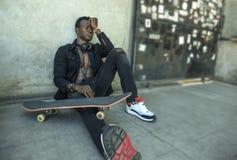 Homem afro-americano preto deprimido e triste novo que senta-se no canto da terra da rua do grunge com o sentimento da placa do p fotografia de stock