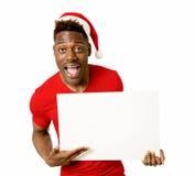 Homem afro-americano preto no espaço feliz de sorriso da cópia do quadro de avisos da placa da exibição do chapéu de Santa do Nat Imagens de Stock Royalty Free