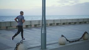 Homem afro-americano que corre na terraplenagem do beira-mar filme