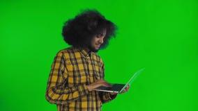 Homem afro-americano que datilografa no port?til Nenhuma cabe?a perto de agita??o Na tela verde ou no fundo chave do croma Concei video estoque
