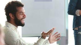 Homem afro-americano que discute com os colegas durante uma reunião video estoque