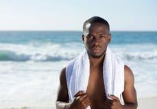 Homem afro-americano que está na praia com toalha Fotos de Stock