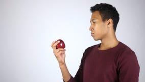 Homem afro-americano que guarda Apple vermelho e que olha Apple Imagens de Stock Royalty Free