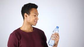 Homem afro-americano que guarda a garrafa da água destilada, fundo branco Fotos de Stock