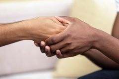 Homem afro-americano que mantém as mãos do fim amado da mulher foto de stock