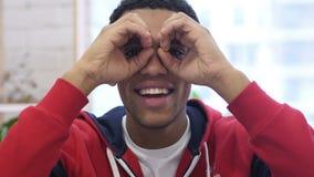Homem afro-americano que procura a possibilidade nova com binocular feito a mão filme