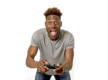 Homem afro-americano que usa o controlador remoto que joga o jogo de vídeo ha Imagens de Stock