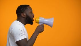Homem afro-americano que usa o megafone para o protesto, chamando à ação, vista lateral filme