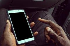 Homem afro-americano que usa o telefone esperto móvel com a tela preta vazia Trocista acima de um dispositivo de terra arrendada  imagem de stock royalty free