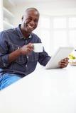 Homem afro-americano que usa a tabuleta de Digitas em casa imagem de stock royalty free
