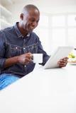 Homem afro-americano que usa a tabuleta de Digitas em casa imagens de stock