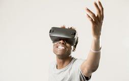 Homem afro-americano que veste os óculos de proteção da visão do vr 360 da realidade virtual que apreciam o jogo de vídeo Imagem de Stock