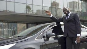 Homem afro-americano satisfeito que cumpriu seu sonho e comprou o carro luxuoso vídeos de arquivo