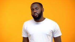 Homem afro-americano virado que olha a c?mera isolada no fundo amarelo fotografia de stock royalty free