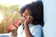 Homem afro de riso que inclina-se contra a parede que fala no telefone celular imagens de stock