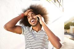 Homem afro feliz na chamada telefônica que anda fora imagem de stock royalty free