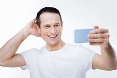 Homem agradável alegre que levanta para o selfie imagens de stock royalty free