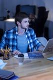 Homem agradável de trabalho duro que olha os gráficos Fotografia de Stock Royalty Free