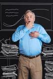 Homem agradável do envelhecimento que está entre pilhas do papel Imagem de Stock