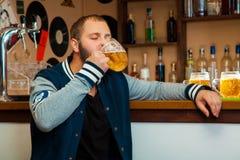 Homem agradável no vidro da bebida da barra da cerveja clara Imagens de Stock