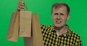Homem agressivo irritado com gritaria dos sacos de compras Chave do croma imagens de stock royalty free