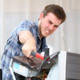 Homem agressivo que bate um computador com um martelo imagens de stock