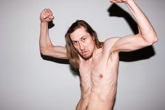 Homem agressivo que mostra fora seus músculos