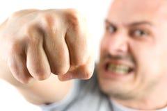 Homem agressivo que mostra seu punho isolado no branco imagens de stock