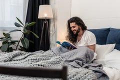 Homem alegre agradável que senta-se na cama imagem de stock