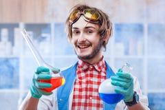 Homem alegre com garrafas da química fotos de stock