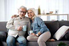 Homem alegre e mulher maduros que descansam no sofá em casa imagens de stock royalty free