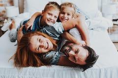 Homem alegre e mulher que jogam com crianças fotografia de stock