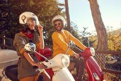 Homem alegre e mulher que montam um 'trotinette' e que t?m o divertimento foto de stock royalty free